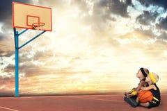 Zwei Brüder, die Basketball in der Straße spielen Rest während des Bruches stockbilder