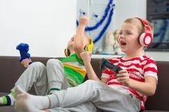 Zwei Brüder, die in den Kopfhörersteuerknüppeln in den Videospielen spielen lizenzfreie stockbilder
