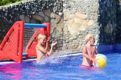 Zwei Brüder, die mit Ball im Swimmingpool spielen Stockbilder