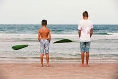 Zwei Brüder eines Jugendlichen, der auf dem Ozean, die Freundschaft O spielt lizenzfreie stockfotografie