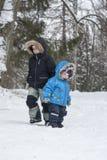Zwei Brüder im Winterschneewald gehen zum gegenüberliegenden destina stockbild