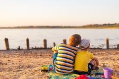 Zwei Brüder, Jungen 3 Jahre und 9 Jahre alt, passen den Sonnenuntergang auf dem See auf lizenzfreies stockbild