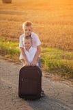 Zwei Brüder mit einem Koffer auf der Straße im Sommer bei Sonnenuntergang Stockbild