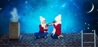 Zwei Brüder sitzen Heiliger Nacht auf dem Dach vor und trinken heißen Tee von einer Thermosflascheflasche Frohe Weihnachten und f stockbild