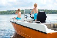 Zwei Br?der schwimmen auf einem Motorboot auf dem See stockfotos