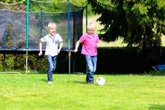 Zwei Brüder, die Fußball im Garten spielen Stockfotos