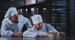 Zwei breite schöne Kerle im einheitlichen Blick der Bäcker auf diesen reichen und appetitanregenden Kuchen und ihn mit Erstaunen  stock video