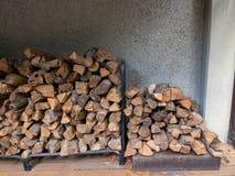 Zwei Brennholzstapel im Freien im bewölkten Gebäude im Freien Lizenzfreie Stockfotos