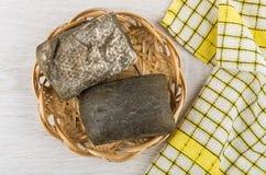 Zwei Brote ciabatta im Weidenkorb und in der gelben karierten Serviette Stockbilder