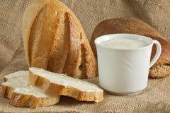 Zwei Brote mit Cup saurer Sahne auf Segeltuch bauschen sich Stockfotos