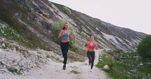 Zwei brunette Damen, die stark mitten in Berg mit Straßensteinen sie glücklich laufen lassen, das Training zusammen genießend her