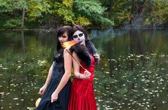 Zwei Brunettesfrauen mit Make-up mögen einen Halloween-Schädel und hallo Lizenzfreies Stockbild