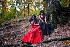 Zwei Brunettesfrauen mit Make-up mögen einen Halloween-Schädel und hallo Lizenzfreie Stockbilder