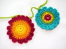 Zwei bunt, gewirkte Blumen auf einer Kette Lizenzfreie Stockbilder