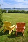 Zwei bunte adirondack Stühle stellen den Hafen gegenüber Lizenzfreies Stockfoto