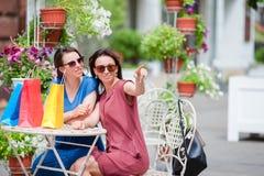 Zwei bunte Käufer der Mode mit Taschen kaufend mit einem intelligenten Telefon im Freiluftcafé Verkauf, Verbraucherschutzbewegung lizenzfreies stockfoto