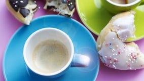 Zwei bunte Tasse Kaffees und Schaumgummiringe lizenzfreies stockfoto