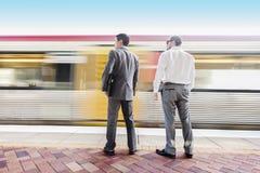 Zwei businessmans, die binden, um im Zug zu erhalten lizenzfreie stockbilder