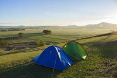 Zwei Campingzelte auf dem Hügel bei Sonnenaufgang Stockbild