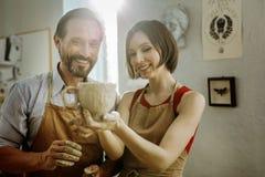 Zwei Ceramists, die nach der Herstellung der netten großen Schale entlastet glauben stockfotos