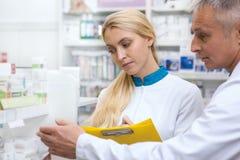 Zwei Chemiker, die am Drugstore zusammenarbeiten stockbild