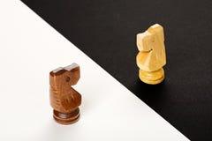 Zwei Chessmen, die nahen Schachvorstand auf hölzernem Hintergrund stehen Stockbilder