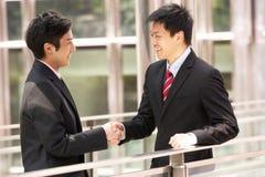 Zwei chinesische Geschäftsmänner, die Hände rütteln Stockfotos