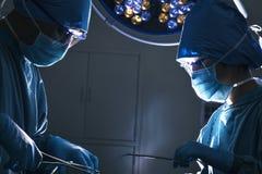 Zwei Chirurgen, die unten schauen und am Operationstisch, dunkler Operationsraum arbeiten Stockfoto