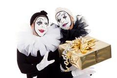Ein Paar blödelt mit einem goldenen Geschenk herum Stockfotos
