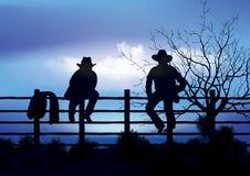 Zwei Cowboys, die auf Zaun sitzen Stockfotografie