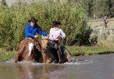 Zwei Cowgirle, die Teich betreten Stockfotos