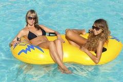 Zwei Damen, die auf aufblasbarem Ring liegen Stockbild