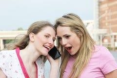 Zwei Damen, die zu einem Handy hören Lizenzfreies Stockbild