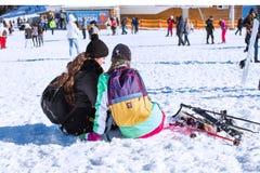 Zwei Damen mit Himmeln stehen das Sitzen auf dem Schnee am Skiort Bansko, Bulgarien still Stockbilder
