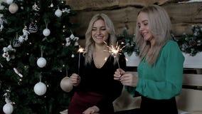 Zwei Damen teilen ihre Gefühle über Weihnachten, das Bengal-Feuer wellenartig bewegt Weihnachten und neues Jahr stock footage