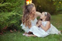Zwei Damenmädchen der blauen Augen der Kastanie der Schwestern blonde, die zusammen Abend des Sommers sonniger Tagesaufwerfen, kl Lizenzfreie Stockfotos