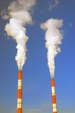 Zwei dampfende Rohre von roten und weißen Farben Hintergrund des blauen Himmels Lizenzfreie Stockbilder