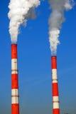 Zwei dampfende Rohre von roten und weißen Farben Hintergrund des blauen Himmels Stockfotografie