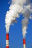 Zwei dampfende Rohre von roten und weißen Farben Hintergrund des blauen Himmels Lizenzfreie Stockfotografie