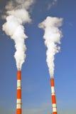 Zwei dampfende Rohre von roten und weißen Farben Hintergrund des blauen Himmels Stockfoto