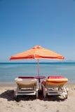 Zwei deckchairs unter Sonnenschirm auf Strand Stockbilder