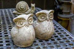 Zwei dekorative Figürchen einer Eule und der Schnecke Lizenzfreie Stockfotos