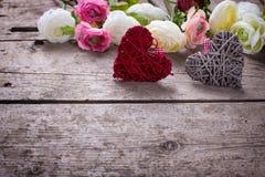 Zwei dekorative Herzen und Blumen auf hölzernem Hintergrund der Weinlese Stockfotos