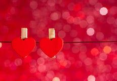 Zwei dekorative rote Herzen, die gegen rotes Licht bokeh Hintergrund, Konzept des Valentinstags hängen Lizenzfreies Stockfoto