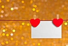 Zwei dekorative rote Herzen mit der Grußkarte, die an goldenem hellem bokeh Hintergrund, Konzept des Valentinstags hängt Lizenzfreies Stockbild