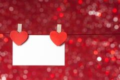 Zwei dekorative rote Herzen mit der Grußkarte, die an rotes Licht bokeh Hintergrund, Konzept des Valentinstags hängt Stockfotografie
