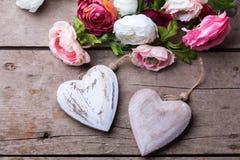 Zwei dekorative weiße hölzerne Herzen und Blumen Stockbilder