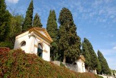Zwei der sieben Kirchen, der Wände bedeckt mit Kapriolen und der großen Zypressen in Monselice durch die Hügel im Venetien (Itali Stockbild