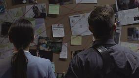 Zwei Detektive, die Links zwischen den Verbrechen betrachten Brett überprüfen und analysieren stock video footage