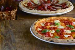 Zwei diente heiße geschmackvolle Pizza mit Pepperonis, Prosciutto, Mozzarella, Kirschtomaten und Basilikum, auf einem dunklen Hol Lizenzfreie Stockfotografie